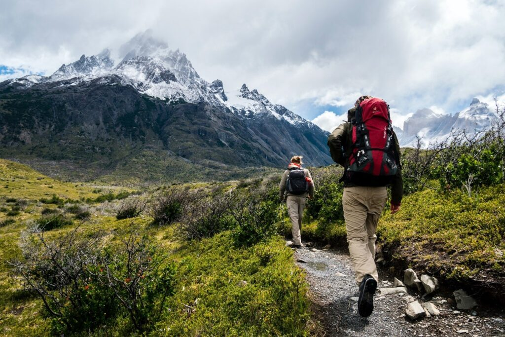 Two people hiking towards a snow-capped mountain